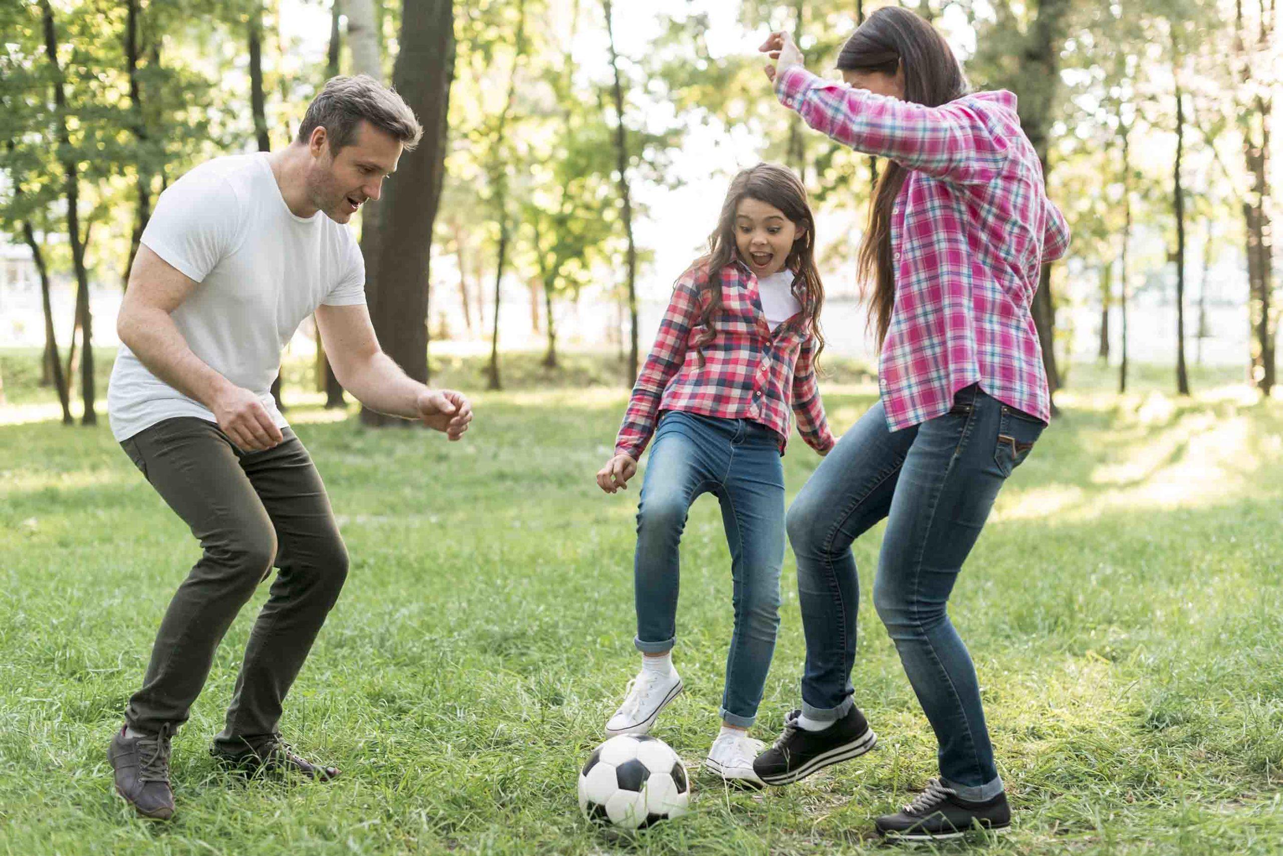 parents et enfants épanouis jouant au football