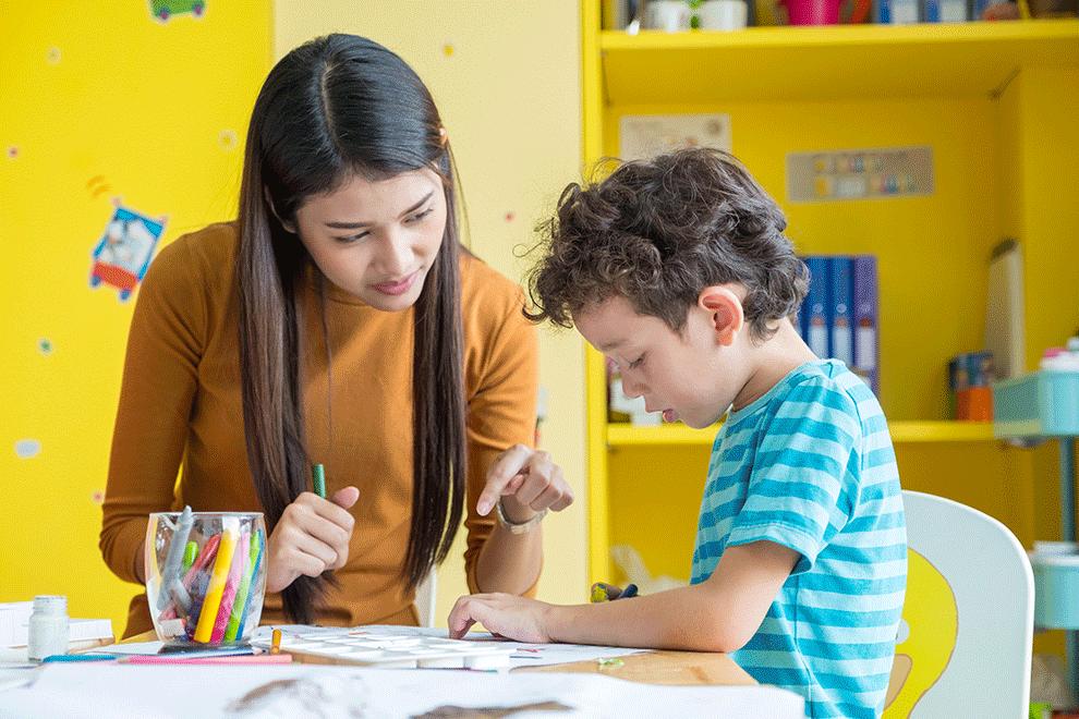 enfant qui dessine avec l'aide de l'assistante maternelle