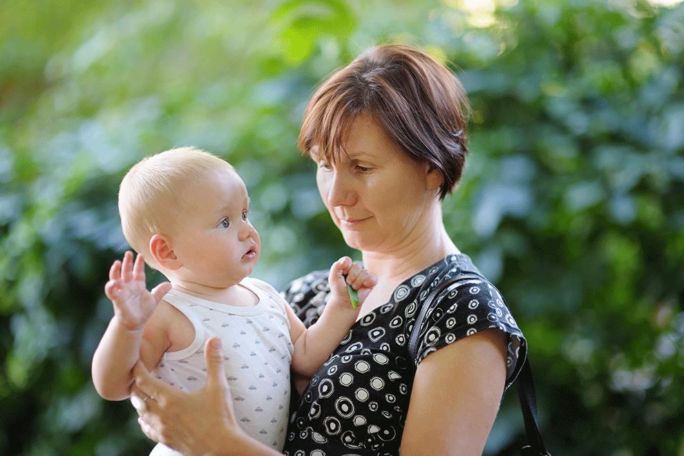assistante maternelle portant un enfant dans les bras
