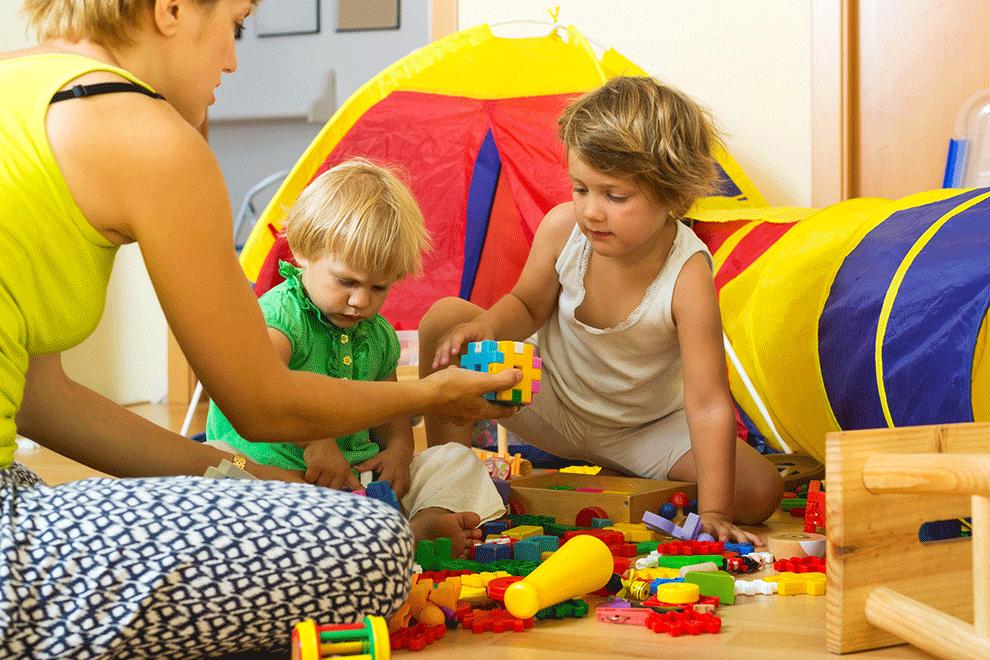 Assistante maternelle jouant avec des enfants