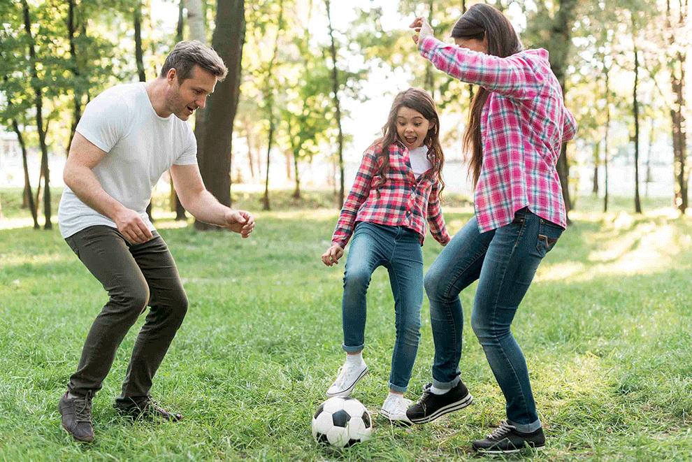parents qui jouent au foot avec leur fille