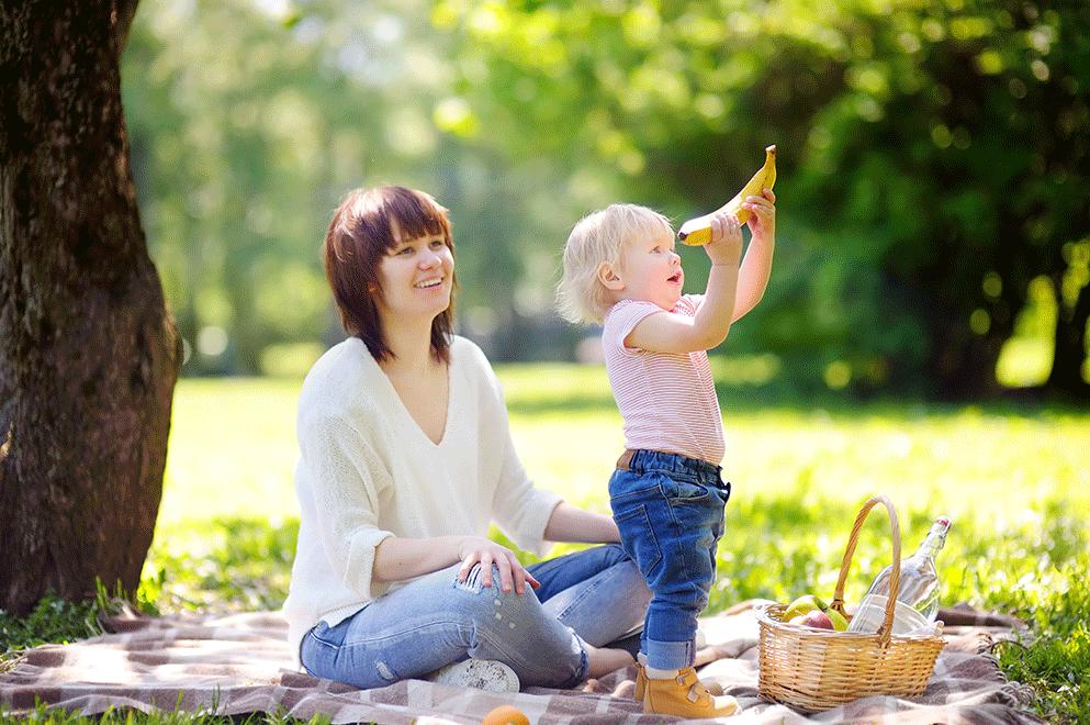 assistante maternelle pic-nic avec un enfant dans un parc